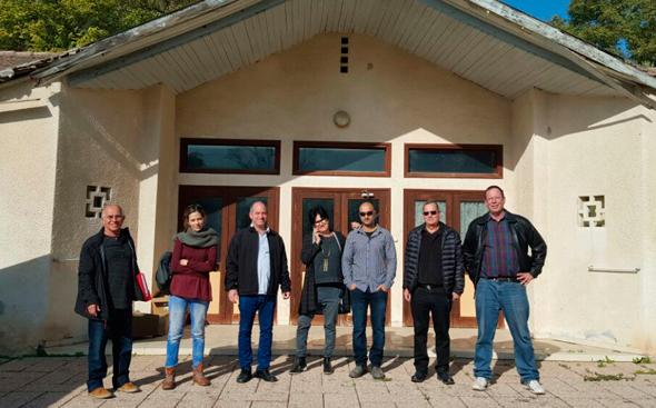 מקימי ומובילי הפרויקט על רקע הבניין בקיבוץ מעוז חיים