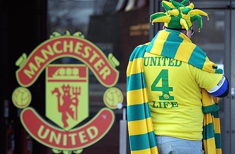 אוהד מנצ'סטר בצבעי המחאה. את הצעיפים והחולצות בצהוב ירוק מוכרים בזול יחסית