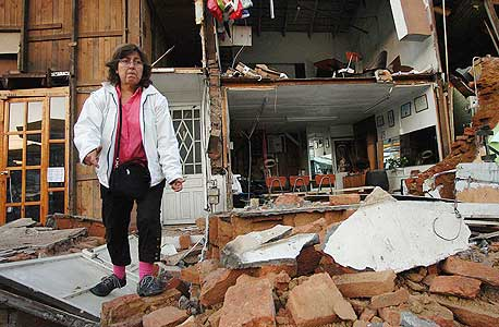 """אשה ליד הריסות ביתה. """"חברות הבנייה התרשלו בשמירה על התקן"""""""