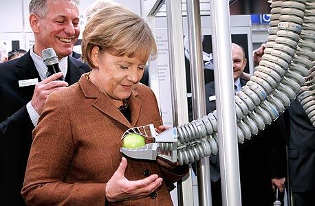 הקנצלרית אנגלה מרקל עם זרוע רובוטית עדינה הפועלית כשריר נוזלי, מבוסס לחץ אוויר