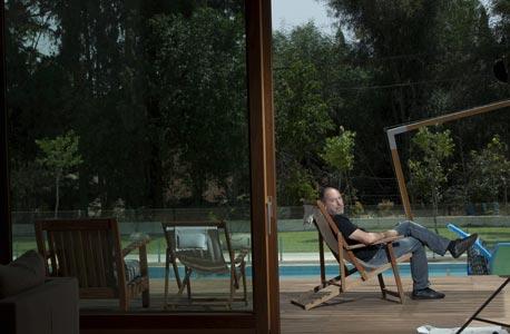 """דני גולדשטיין בחצר ביתו. """"אני פותח את היום בשחייה"""""""