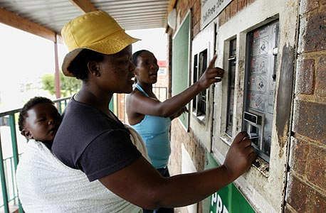 """נשים משלמות מראש במכונות אוטומטיות עבור כמות מוגבלת של חשמל לבתיהן בעיירת עוני ליד יוהנסבורג. """"עורכת דין ניגרית סיפרה לי שחשמל עולה לה 700 דולר בחודש. בשביל רוב האנשים שם זו משכורת שנתית"""""""