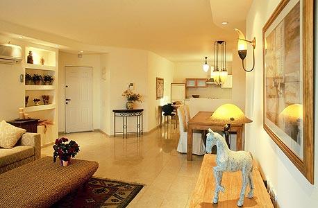 """דירה לדוגמה משנות ה-90 של חברת שיכון ובינוי נדל""""ן. מרצפות קטנות, דלת כניסה סטנדרטית ומטבח בסיסי"""