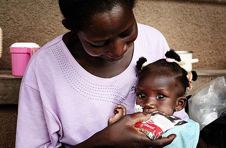 ילדה מבורקינה פאסו אוכלת פלאמפינאט. כל יחידה כזו מכילה כ-500 קלוריות