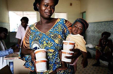 """אמא אוספת קופסאות משפחתיות של פלאמפי-דוז בבורקינה פאסו. """"זו לא תרופת  פלא לכל הרעב העולמי"""""""