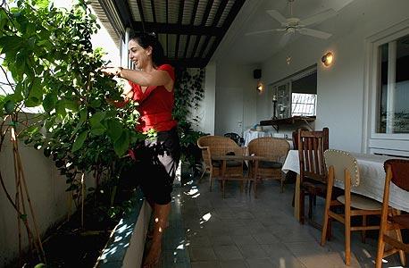 נורית בן-אשר דגני במרפסת ביתה, מטפלת בגינה