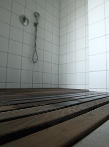 רצפות עץ עמידות למים עם תעלות ניקוז במקלחות. נשפך כסף בלי פרופורציה