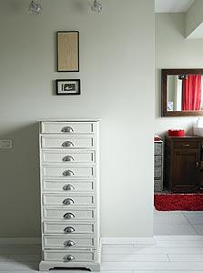 שידת עץ לבנה בחדר השינה שנורית מצאה ברחוב, ומדי תקופה מחליפה את הידיות למגירות