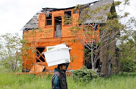 """בית נטוש שנצבע בעתום על ידי קבוצת אמני הגרילה """"אובג'קט אורנג'"""". """"כאן אפשר להוריד את השריון"""", מסבירה האמנית קייט לבנט"""
