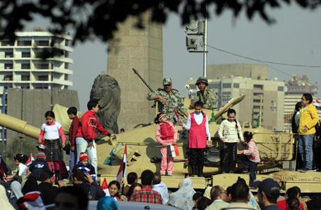 מפגינים מצטלמים למזכרת עם טנקים בכיכר תחריר. הצבא דואג קודם כל לעצמו, צילום: אי פי