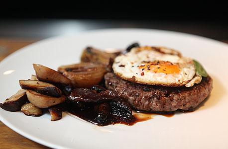 """טוטו, ת""""א. מנה לדוגמה: המבורגר מאנטרקוט טרי עם ביצת עין, רוטב יין ופטריות יער ופורצ'יני טריות"""