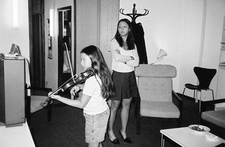 """צ'ואה צופה בבתה סופיה מנגנת. """"אם תיתן לילד בחירה  לשחק במחשב או להתאמן בנגינה, די ברור במה הוא יבחר"""""""