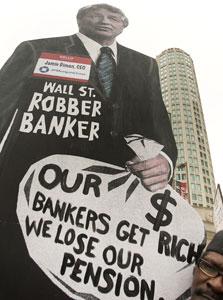 """הפגנה עם תמונתו של ג'יימי דיימון, מנכ""""ל ג'י.פי.מורגן מחוץ לכינוס בנקאי צמרת בשיקגו, 2009"""