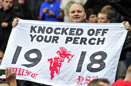 אוהד מנצ'סטר יונייטד עם השלט שמראה לליברפול מי הקבוצה הגדולה באנגליה