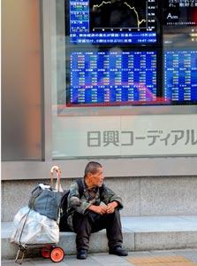 הומלס יפני ליד לוחות המסחר של מדד ניקיי