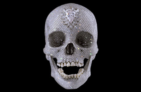 """מה עולה 100 מיליון דולר? """"למען השם""""  של דמיאן הירסט - האמן הבריטי דמיאן הירסט, שמשווים אותו לאמן האמריקאי אנדי וורהול בכך שהפך מיוצר שמבקר את מסחור האמנות לאחד שמפיק יצירות אמנות כעסק כלכלי.  מה עוד אפשר לקנות ב־100 מיליון דולר?  את רשת טיב טעם."""