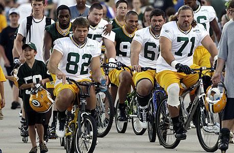שחקני גרין ביי פאקרס רוכבים על אופניים עם האוהדים. כשכולם יכולים להפסיד מהשביתה, אף אחד לא רוצה אותה