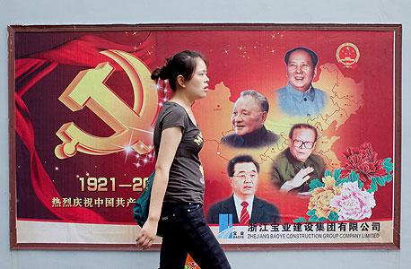 צעירה סינית בשנגחאי על רקע פוסטר המציין 90 שנה למפלגה הקומוניסטית. נציגיה ממשיכים לשלוט בעולם העסקים
