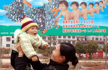 במרכז: כרזה סינית שמעודדת הולדת ילד אחד למשפחה, צילום: איי אף פי