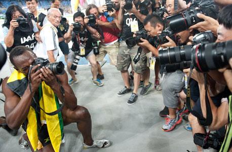 יוסאיין בולט מבלה עם הצלמים. קשה לגייס כספים גדולים מזכויות השידור, צילום: MCT