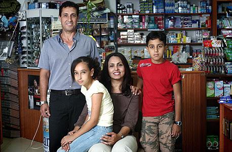 """משפחת מחמיד. בסאם (48), אמל (37), מגד (13) ויארה (11), רוקח ועובדת סוציאלית, אום אל־פחם. """"זה מעמד הביניים - כל הזמן את חייבת להתאמץ, כל הזמן את רצה כדי לחיות בכבוד ואף פעם לא מספיקה, כל הזמן נלחמת במינוס. במישור המשפחתי לא תוכלי אפילו לחשוב על כמה ילדים שאת רוצה. היה לי חלום להיות אמא לארבעה ילדים, אבל אם את רוצה רמת חיים טובה לילדים,  אי אפשר"""""""