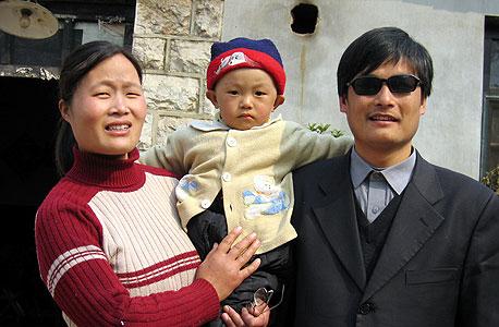 צ'ן, אשתו ובנם הפעוט מחוץ לביתם שהפך לכלאם, 2005