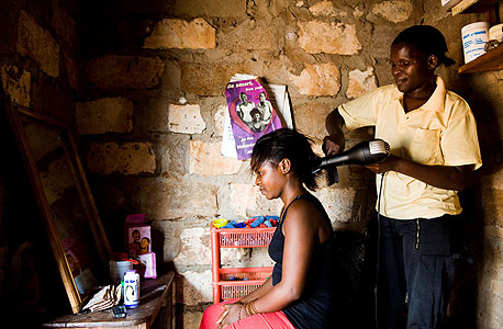 זמביה: ספרית מייעצת ללקוחה על שימוש בקונדום, בניסוי של מעבדת העוני שבו ספרים שימשו כסוכנים להפצת אמצעי מניעה בקהילה
