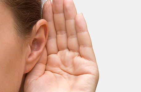 A person holding their hand to their ear. Photo: Shutterstock