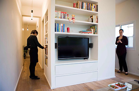 הטלוויזיה בסלון ומעליה מדפי הספרים