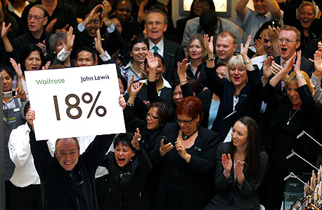 עובד בחנות של ג'ון לואיס באוקספורד סטריט בלונדון חושף, כמדי שנה, שלט ובו גובה הבונוס השנתי שיקבלו העובדים, מרץ 2011