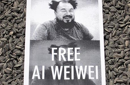 """כרזה הקוראת לשחרור איי מונחת על העבודה הנודעת שלו """"זרעי החמנייה"""" בטייט מודרן, לונדון"""