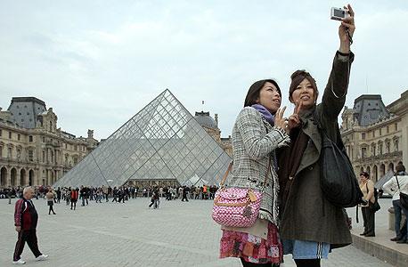 """תיירות יפניות מנציחות את ההמתנה בתור ללובר בפריז. מק'קנל: """"אולי באמת יום אחד יישארו רק תורים"""""""