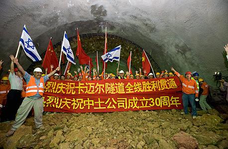 פועלים סינים וישראלים חוגגים את סיום העבודות בפרויקט מנהרות הכרמל