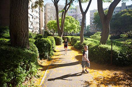 גדי ונעמה פלם, שמשפחתם החליפה בתים, בגינה השכונתית בקריית אונו , צילום: תומי הרפז