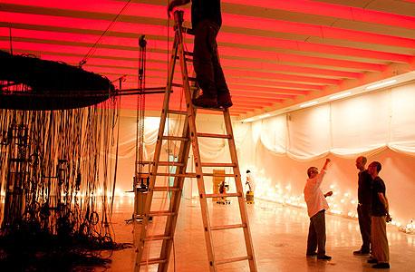 צוות המוזיאון מקים את התערוכה. 799 מנורות פלורסנט