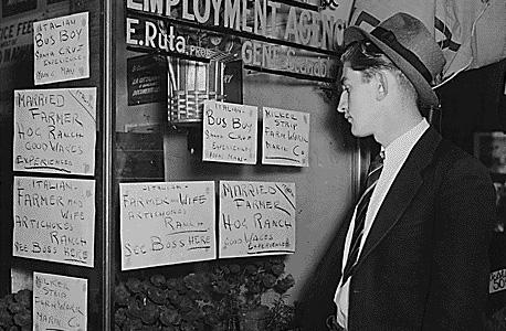 """מובטל אמריקאי מעיין במודעות התלויות על חלון סוכנות תעסוקה בסן פרנסיסקו בשפל הגדול של שנות השלושים. """"לכלכלת שפל צריך לגשת באופן שונה"""""""