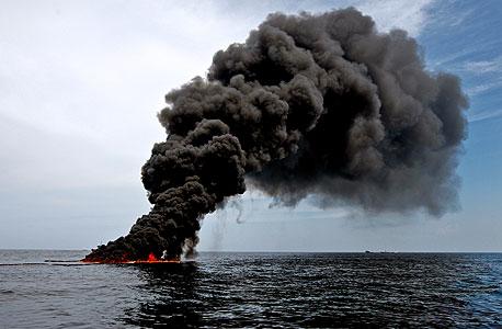 """עשן מיתמר מאסדת הקידוח  של BP במפרץ מקסיקו. המדענים מראשות הפיקוח נתנו לעובדי החברה למלא את הדו""""חות בעצמם"""