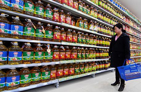 """אשה מול מדף בקבוקי שמן בסופרמרקט בסין. """"החברה שלנו מאורגנת סביב הגדלת הלחץ לצרוך"""""""