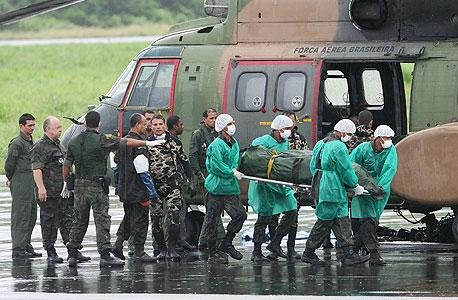 צוות חילוץ ברזילאי מפנה את גופות אחד ההרוגים