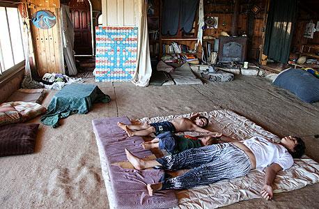 """שלי והילדים בבית האם של גינת שלום אדמה. ברקע לוח השנה של בני המאיה. """"בלוח השנה שלנו, הזמן הוא אמנות"""""""