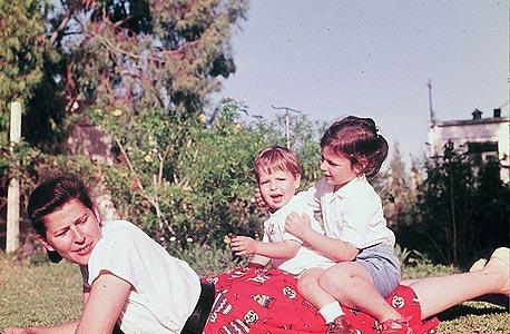 1958. חגית מסר־ירון, בת ארבע וחצי, עם אחיה יואב, בן שנה וחצי, ואמם בחצר ביתם ברמת השרון