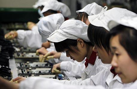 שורות העבדים. פועלי ייצור בקו מוצרי אפל בפוקסקון, צילום: איי פי