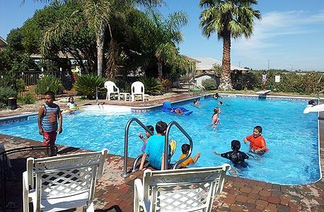 ילדים ממשפחות מצוקה בסטוקטון משתכשכים בבריכה בביתם של ביל וסינדי
