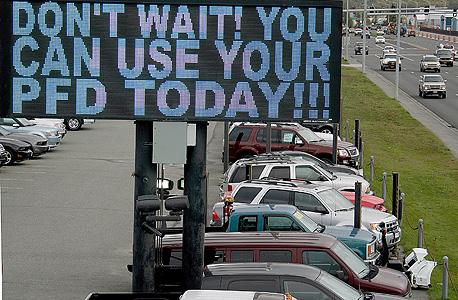 אחד משלטי המכירות שמציפים את אלסקה עם חלוקת הדיבידנד וקוראים לאזרחים לבזבז אותו עוד היום