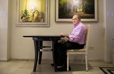 """דובי שיף במלון מרינה, על רקע העבודות """"יער II"""" של אלדר פרבר (מימין) ו""""שלושה בכיוונים שונים"""" של סיגל צברי. """"לא בודק אם אני עומד להרוויח או להפסיד. אם אני אוהב, אני קונה"""""""