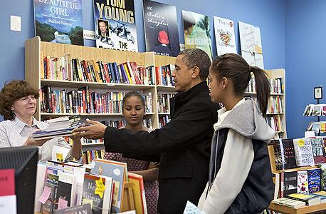 """נשיא ארה""""ב ברק אובמה ובנותיו בחנות ספרים בארלינגטון וירג'יניה עשו קניות כדי לעודד עסקים קטנים, צילום: איי פי"""