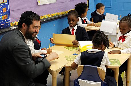 """וורונקר עם תלמידים בבית הספר בניהולו, P.S. 770 בברוקלין. """"אני רוצה לראות את המודל הפרוסי־תעשייתי במערכת החינוך מושמד"""""""