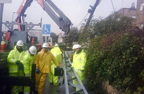 עובדי חברת החשמל מתקנים את נזקי הסערה