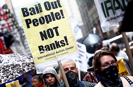 """הפגנה בניו יורק נגד תוכנית החילוץ של הבנקים, 2008. """"החילוץ בוצע בחוסר הוגנות עמוק. אלה שגרמו למשבר זכו לתגמול נדיב, ולוקחי המשכנתאות, מעמד הביניים, זכו להתעלמות"""""""