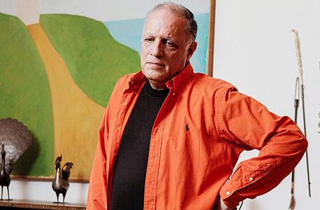 """אילן שבתאי בביתו בירושלים, על רקע """"בית על ההר"""" של אורי ריזמן. """"את רואה את הגבעה בציור? מתישהו אני אוכל לקנות את הגבעה במחיר שאני אמכור את הציור"""""""
